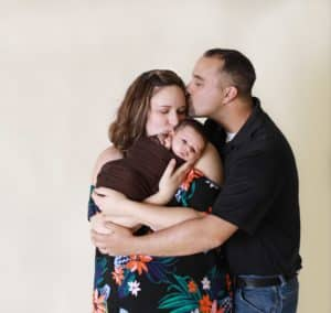 new mother and father kissing newborn baby in Auburn Maine studio