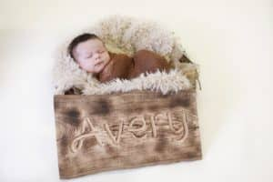 Newborn boy laying in next basket with a name sign and burlap