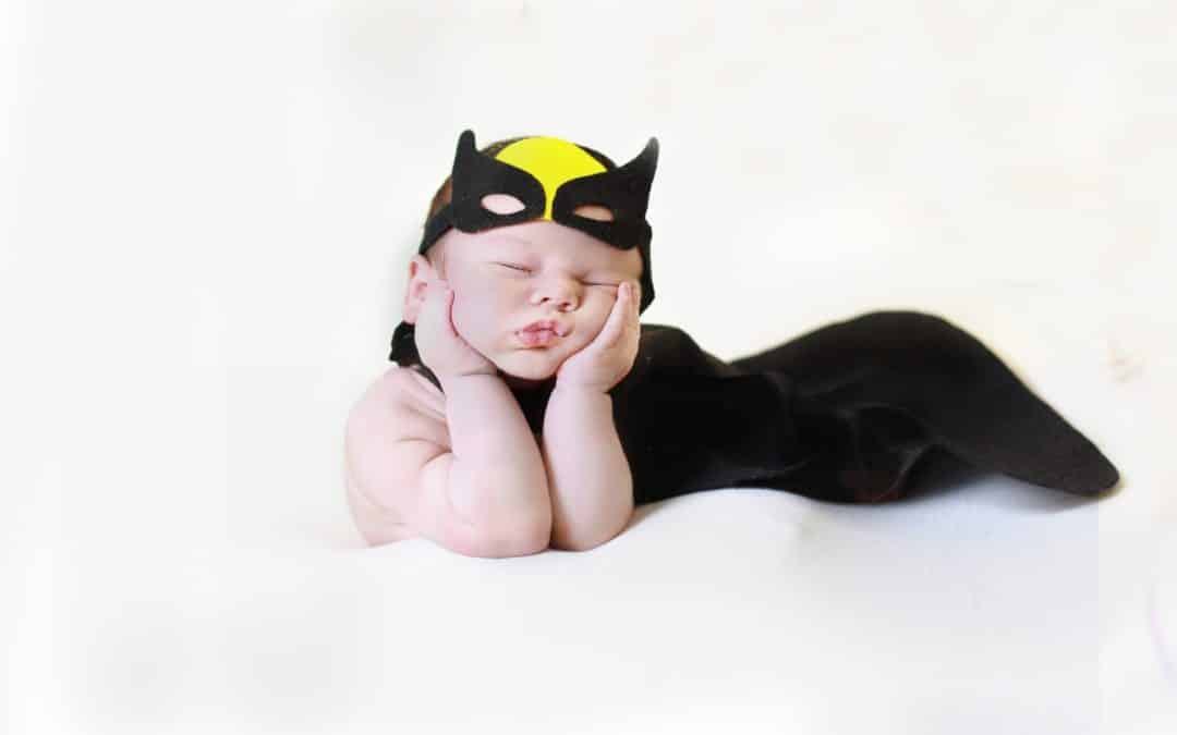 Sleeping newborn baby in a superhero suit