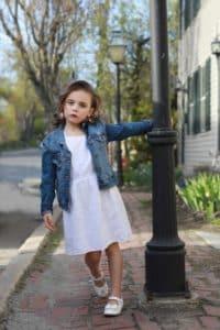 Portland Maine Portrait Photographer, girl in white dress and blue jean jacket swinging around light pole