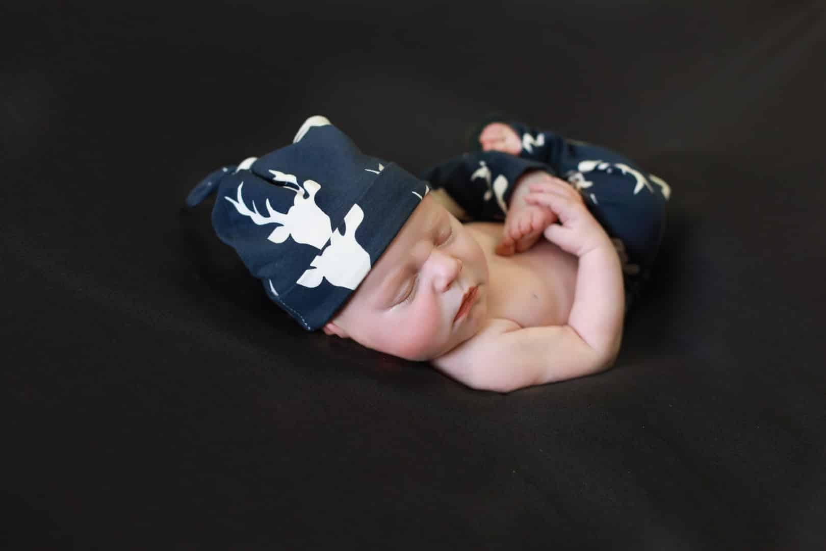 baby sleeping, grabbing foot, navy blue deer hat and pants