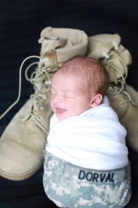 newborn wrapped in white in military hat with military boots on black backgroun