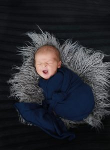 newborn wrapped in blue wrap on grey fur and black background yawning