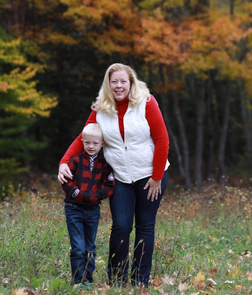 mothers arm around son, standing in open field with fall trees in the background