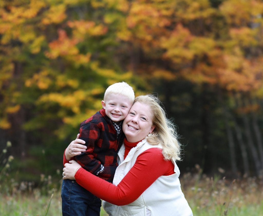 mom bent down hugging her son, fall trees in the background