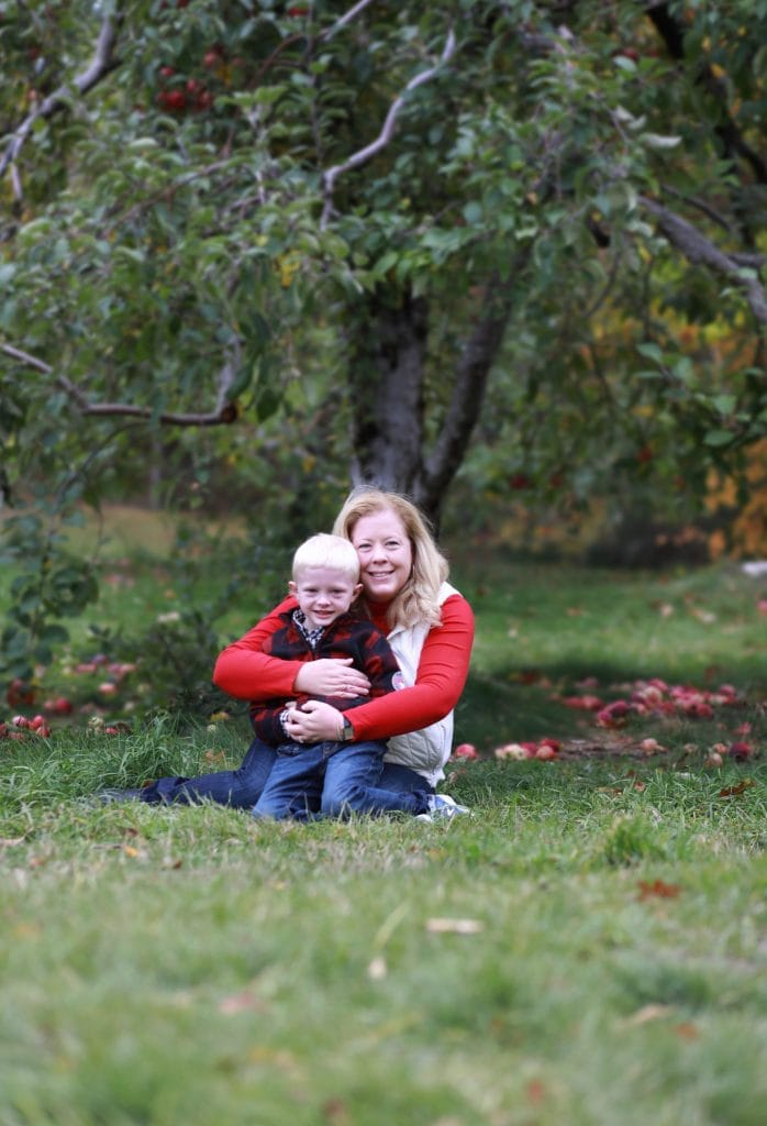 mom and son sitting under an apple tree, mom hugging son from behind, apples around them