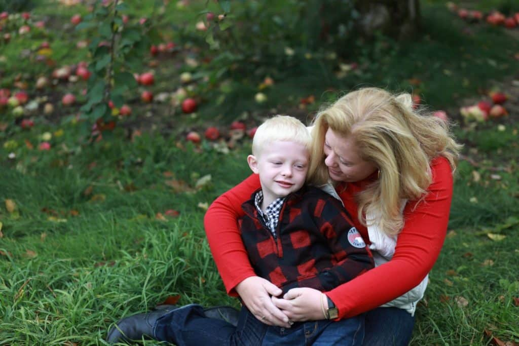mom and son sitting under an apple tree with apples around them, mom hugging son from behind looking at him smiling.
