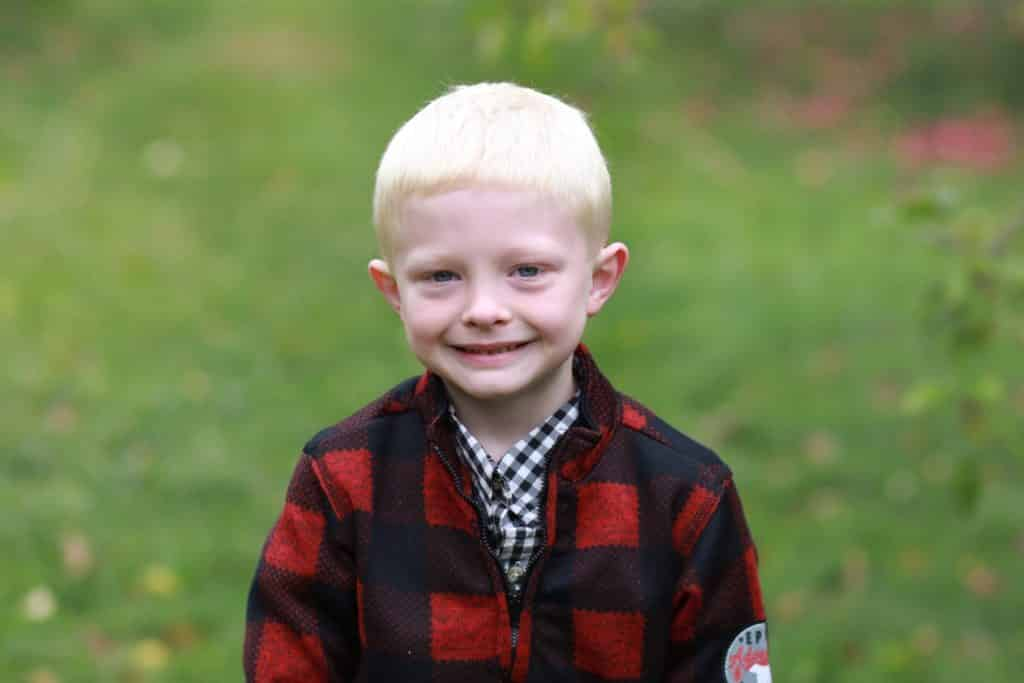 boy in plaid jacket standing in apple orchard starring at the camera with a smile.