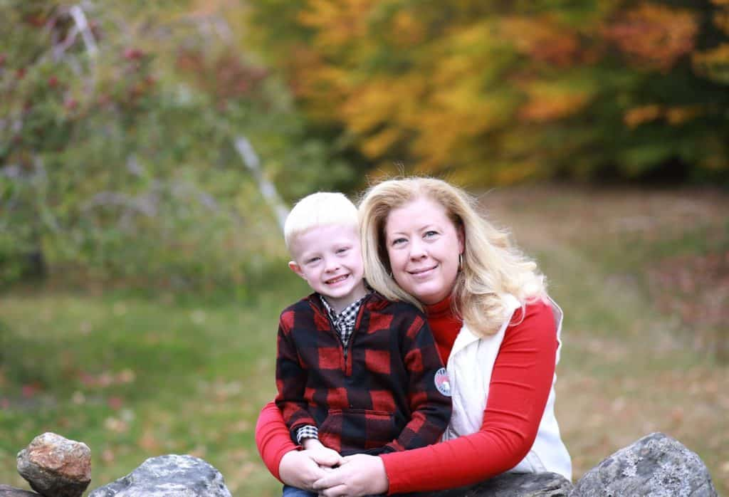 mom hugging son from behind rock wall, fall trees in the background