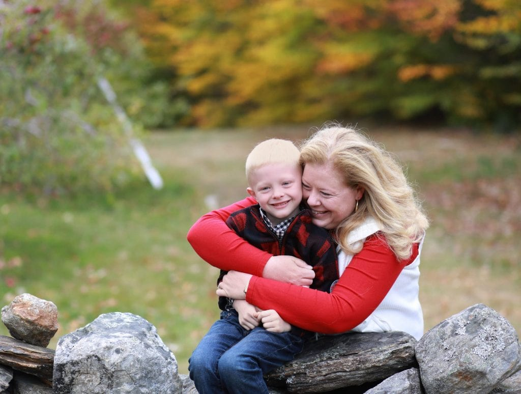 mom looking at son hugging her son from behind rock wall, fall trees in the background