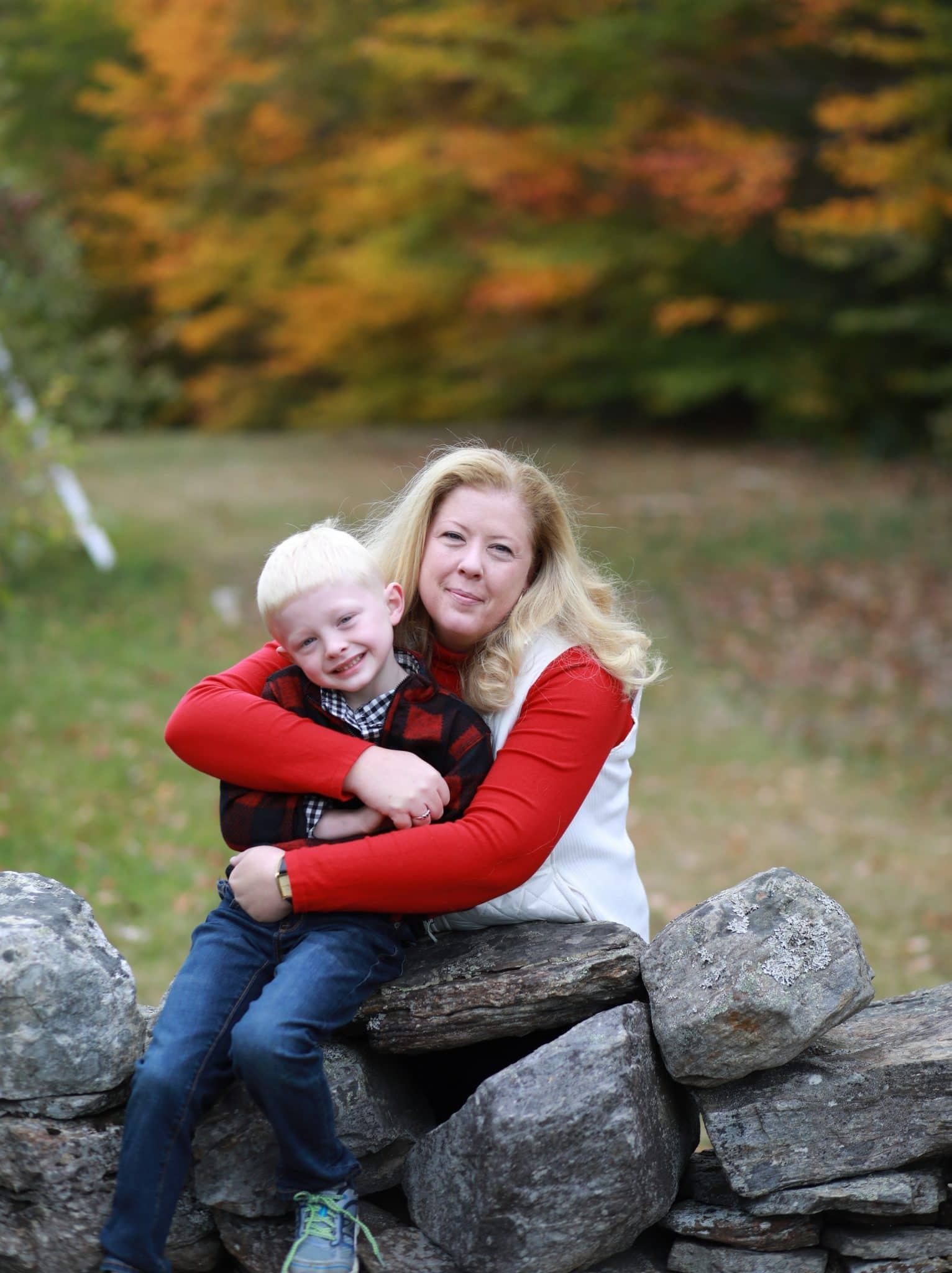 mom hugging son from behind, on stone wall, in apple orchard, fall trees in the background