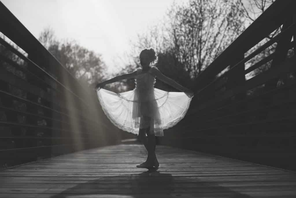 Young white girl dancing on a bridge holding her dress out in black and white