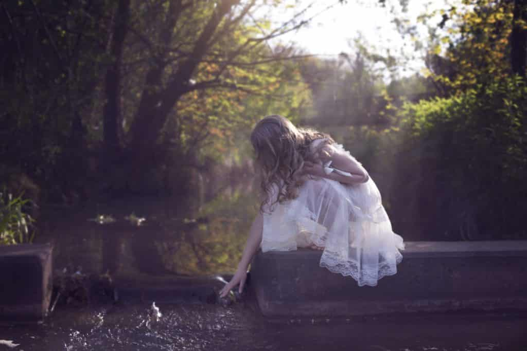 young white girl dressed in white vintage dress reaching down and touching the water facing away from the camera