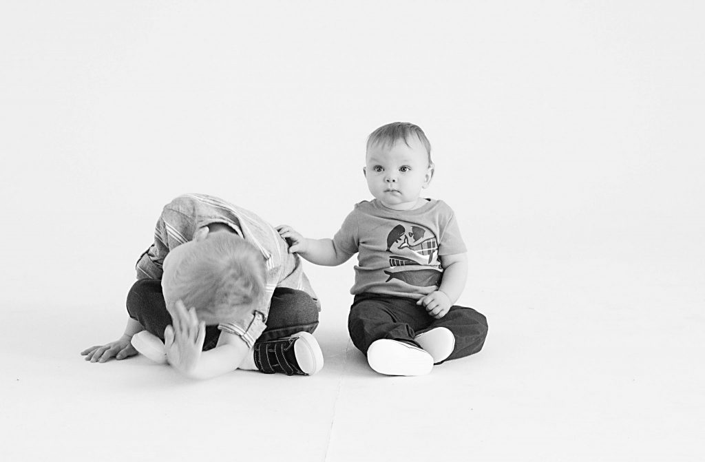 black and white of one year old and brother playing, older brother leaned over himself while younger brother pats his back