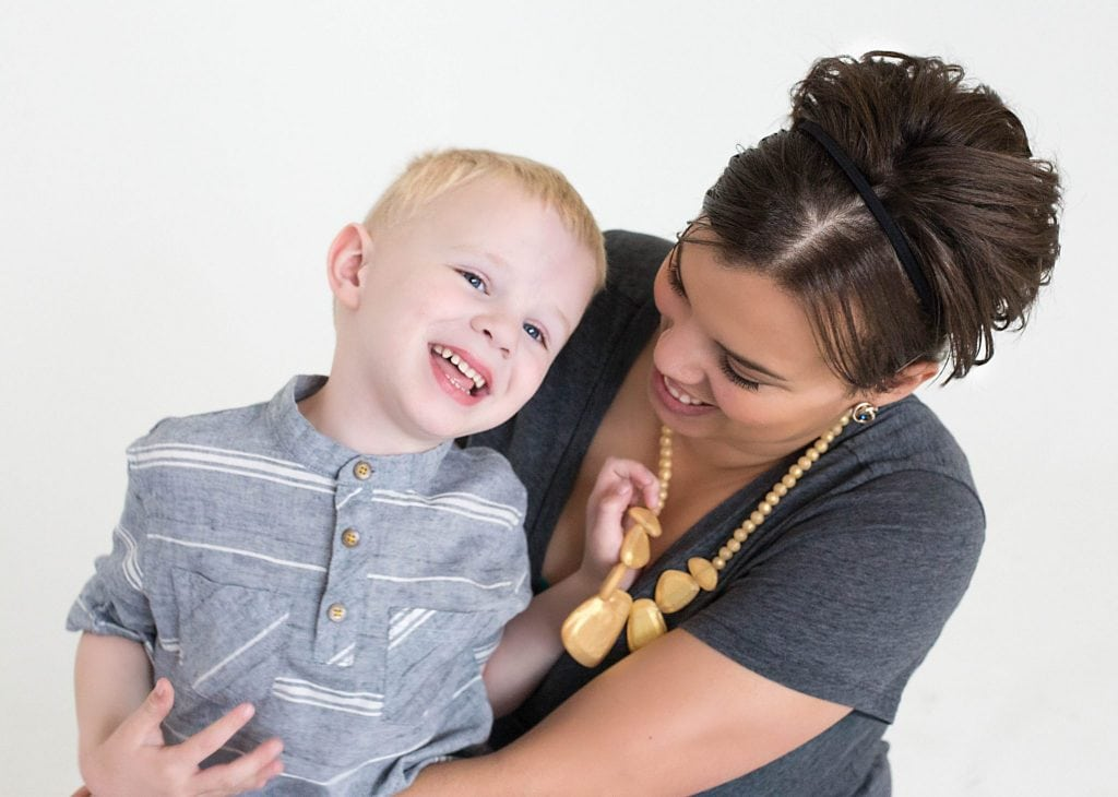 mom holding and looking at her oldest son, he is laughing and playing with her yellow neckless