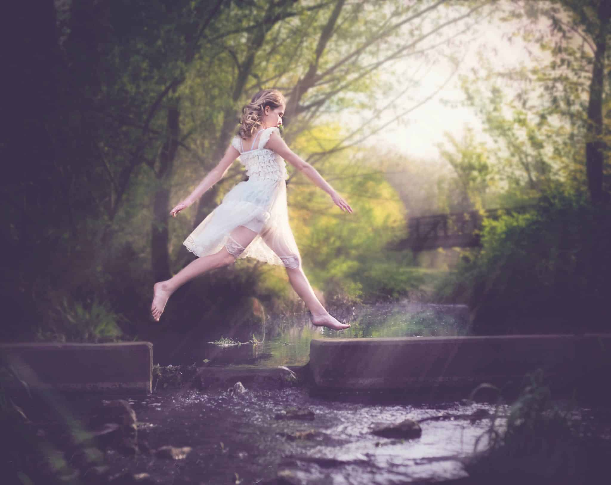 young white girl dressed in white vintage dress jumping over water with sun coming in from the right