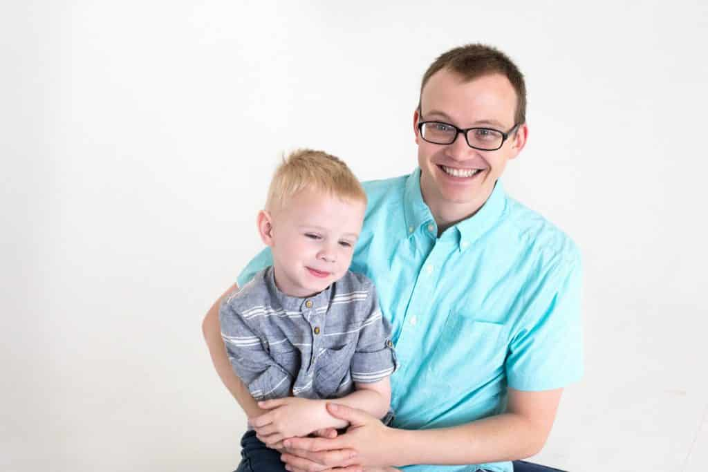 dad smiling, looking at camera, holding oldest son