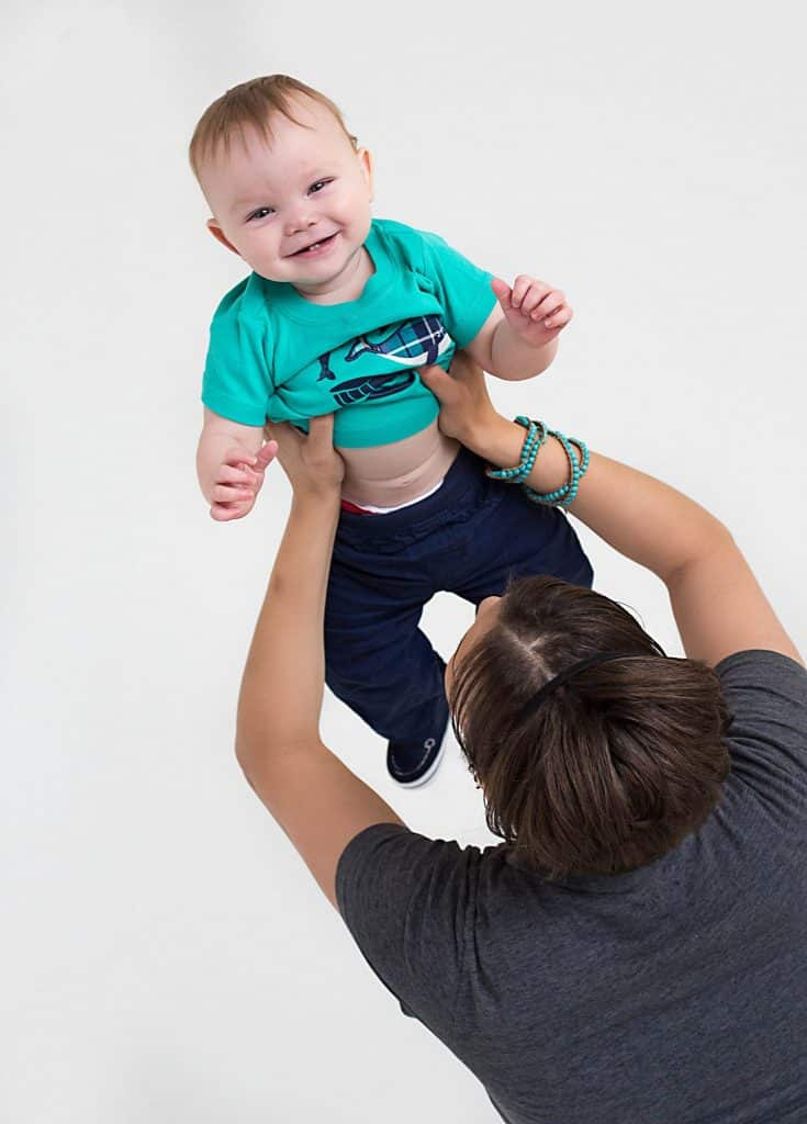 mom facing away from camera, holding youngest son in the air