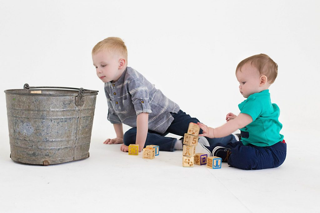 one years old and brother playing with toys on a white background