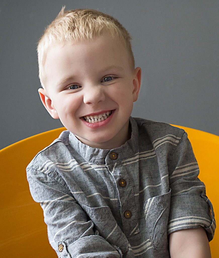 oldest son sitting in yellow chair, smiling big at the camera