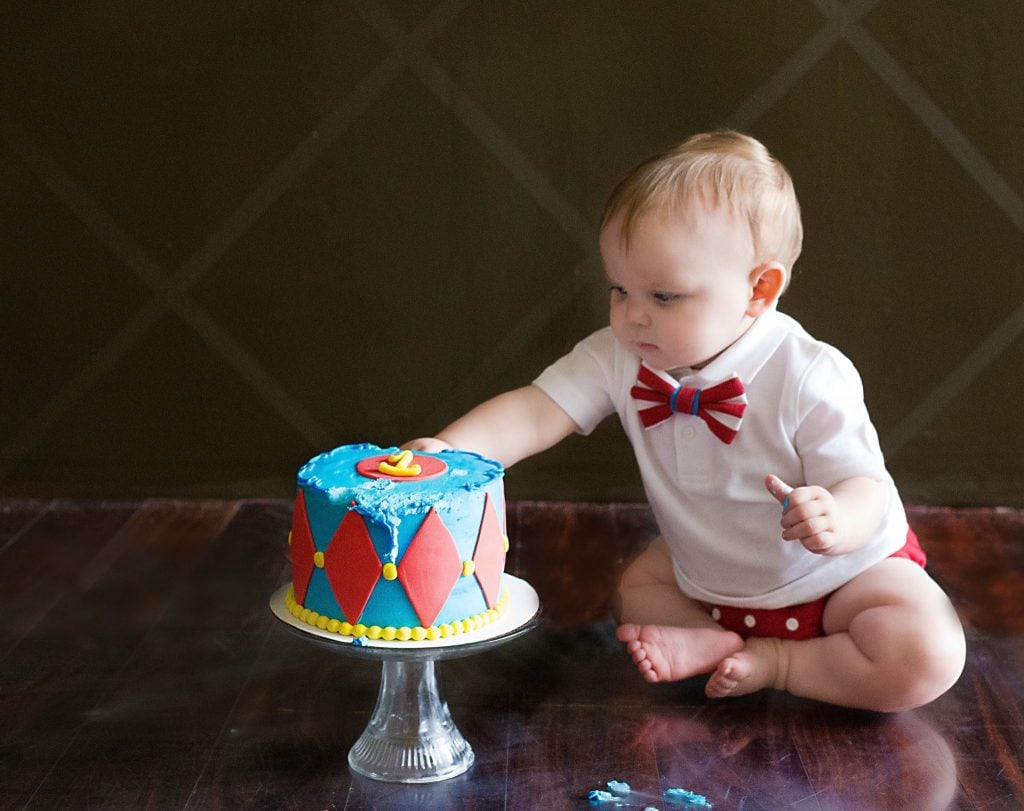One Year old diving into his blue and red circus cake on brown hard wood floor