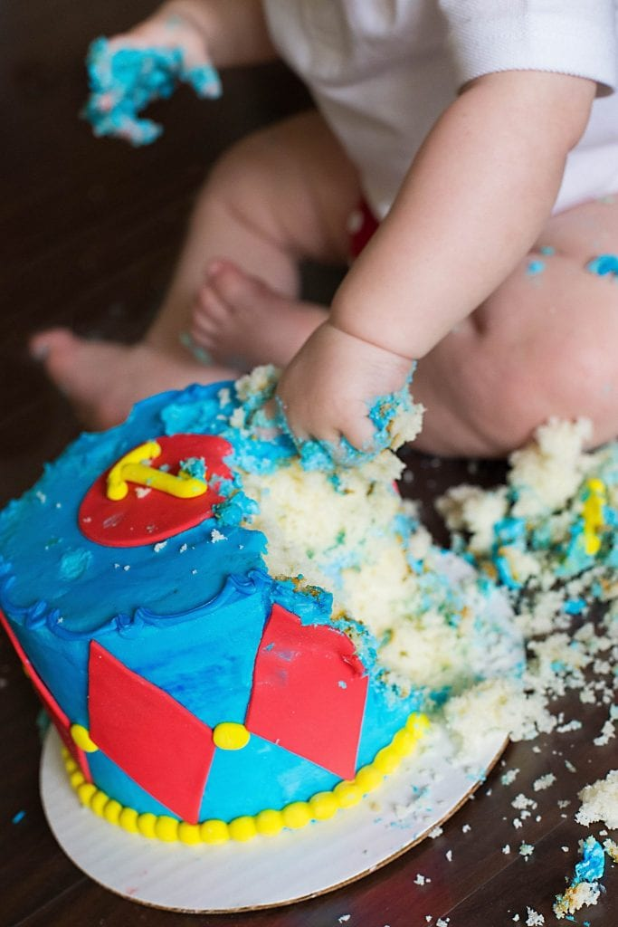 one year old hand diving into blue and red circus cake