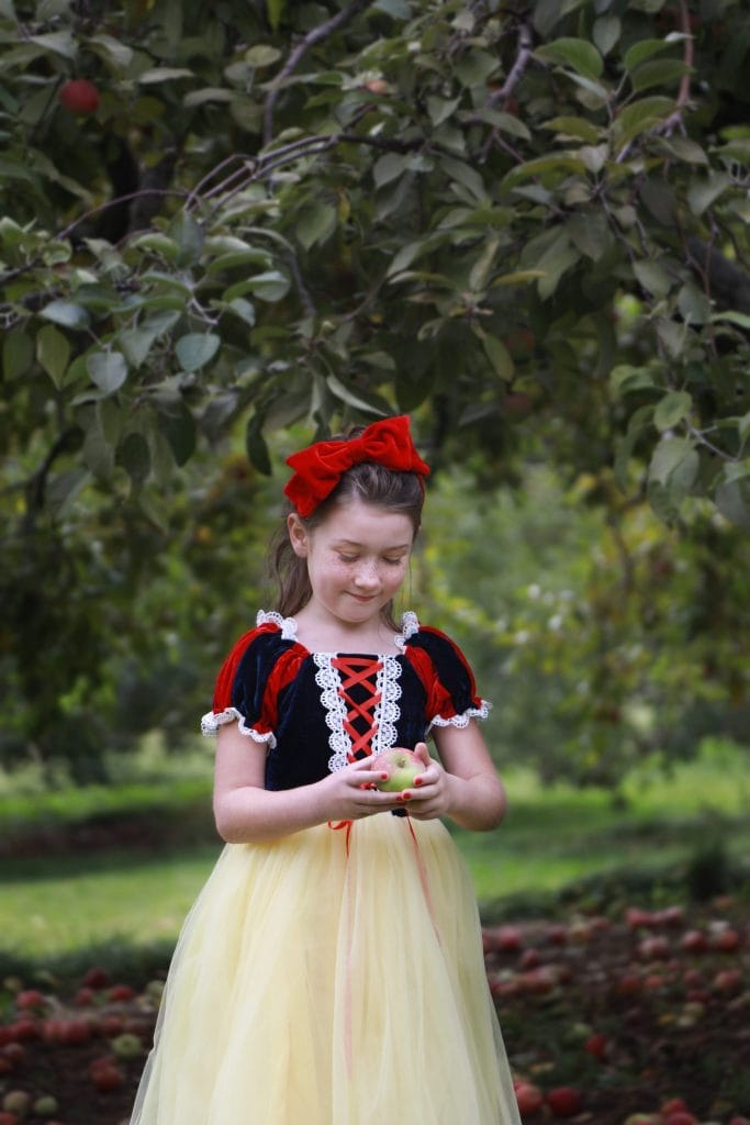 Little girl dressed up as snow white holding a red apple looking down happily at the apple