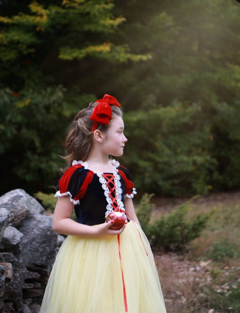 little girl dressed as snow white holding an apple near grey stone wall looking out to the pple orchard, light shining down on her