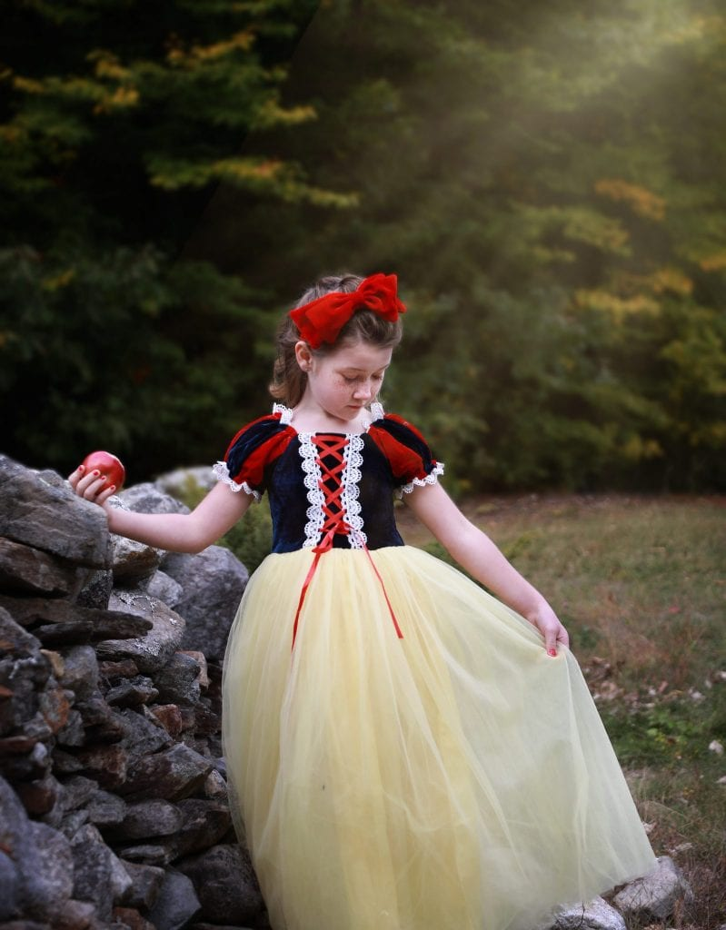 Little girl dressed up as snow white leaning on a grey stone wall holding out her dress looking down, apple in hand