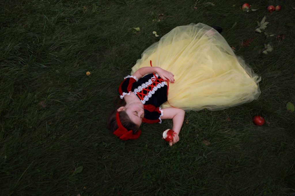 Little girl laying in grass holding a bitten red apple pretending to sleep