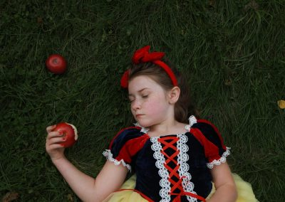 little girl laying on grass dressed up as snow white, holding a bitten apple with her eyes closed.