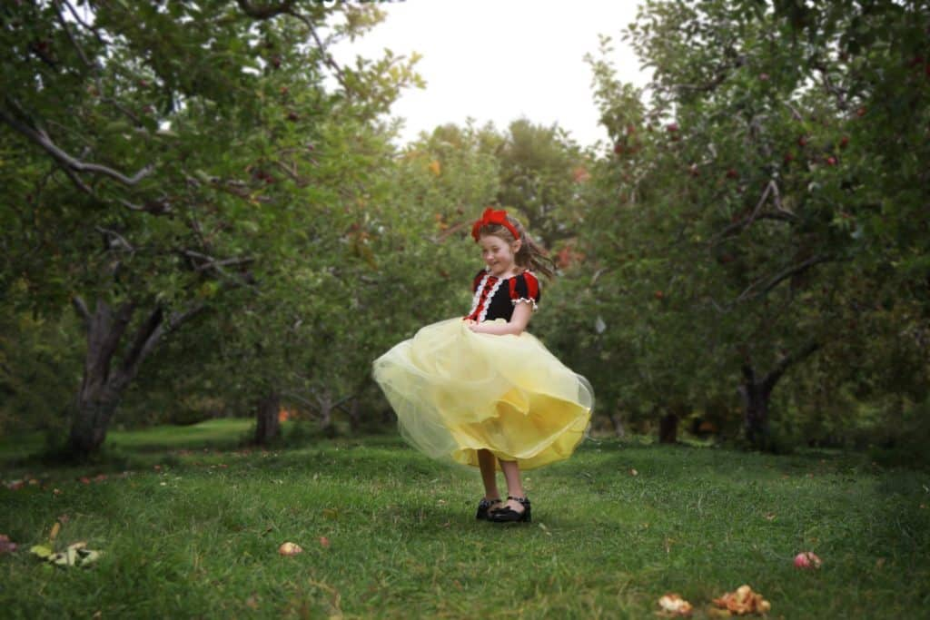 little girl dressed up as snow white twirling around in apple orchard