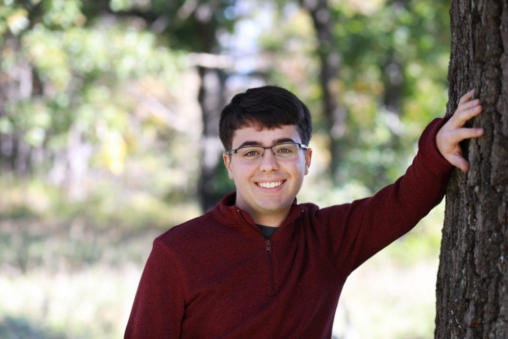 senior boy leaning against a tree with one arm up, the other at his side, wearing glasses and a red shirt, smiling, teeth showing