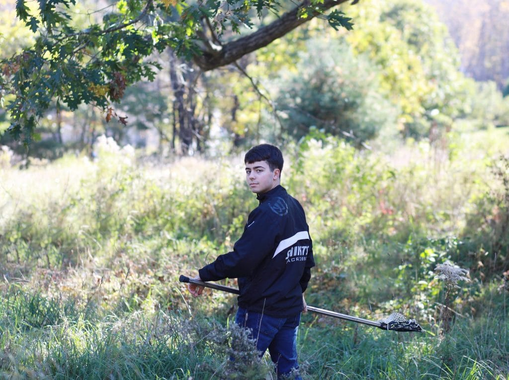 senior boy wearing custome lacrosse jacket, standing in an open field, back facing the camera, turning his head to the camera holding his lacrosse stick