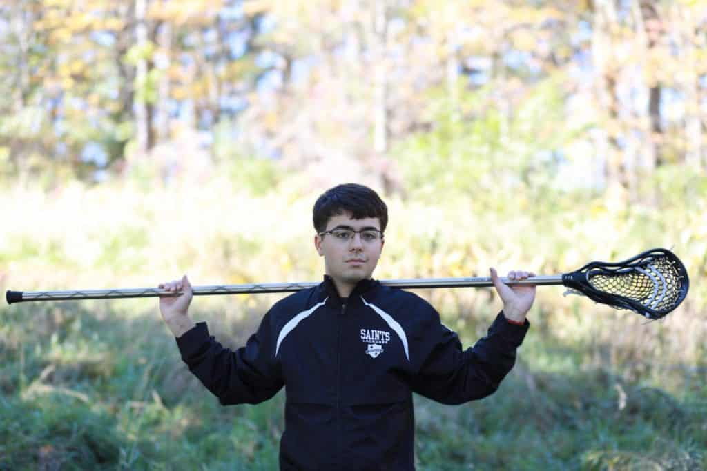 senior boy standing in a field holding his lacrosse stick on his shoulders wearing his lacrosse jacket with his glasses