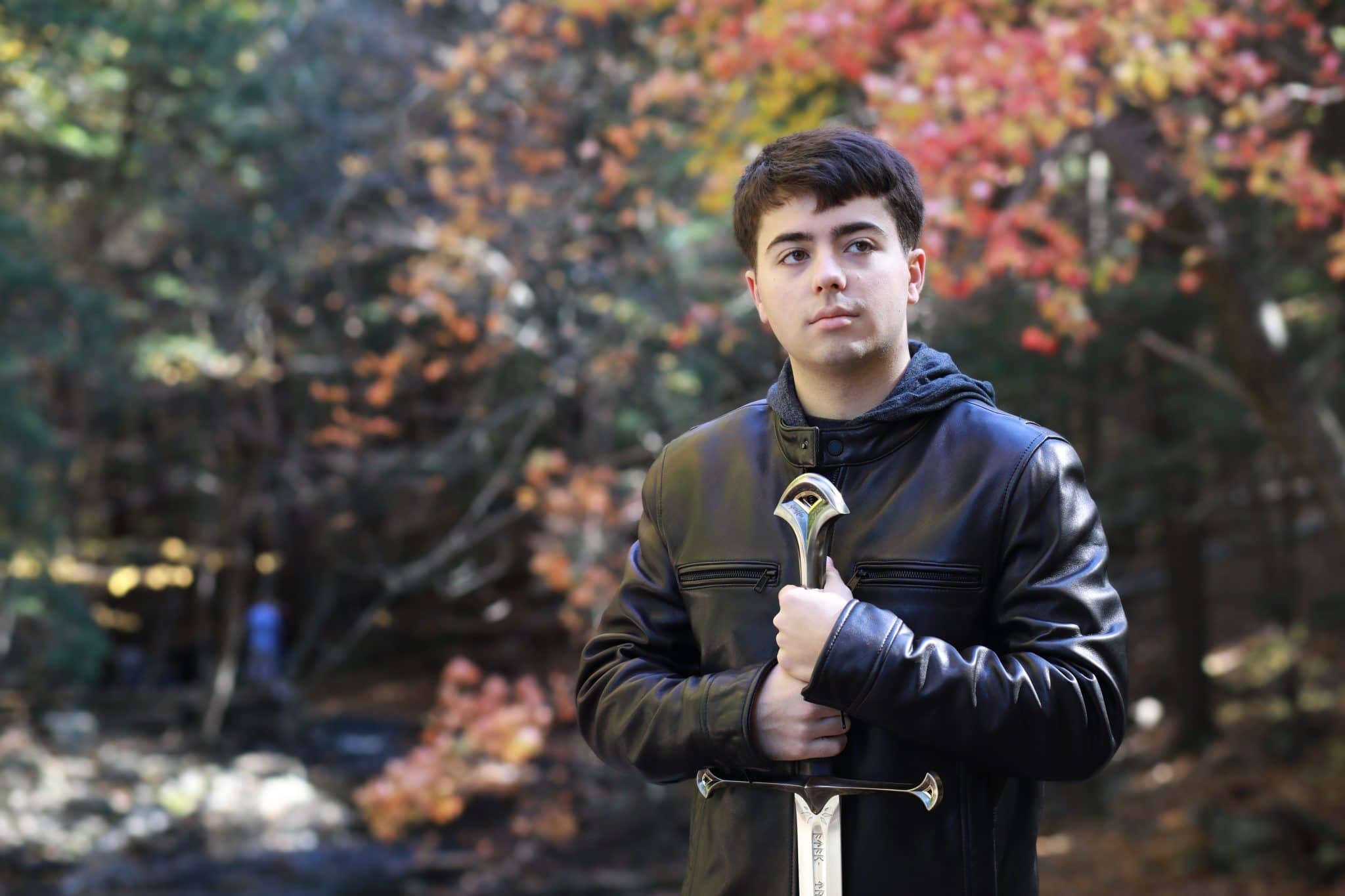 Senior boy in leather jacket holding a giant sword on a bridge with fall colored trees in the background
