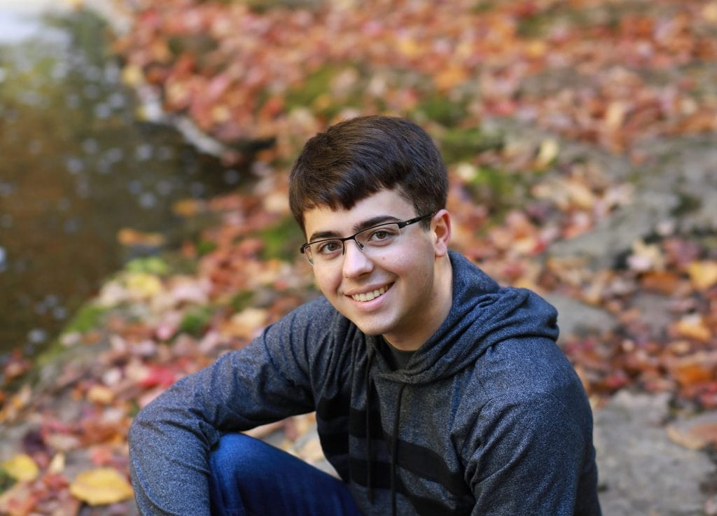 senior boy sitting with elbow on knee, near the stream with fall colors surrounding him, wearing classes and a grey shirt with blue jeans.