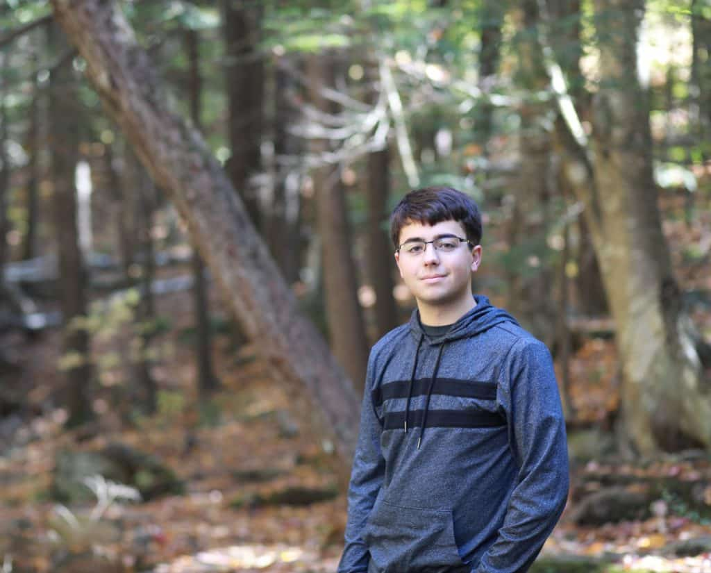 Young man senior in High School in the woods, hands in pocket, wearing glasses, surronded by fall colors on the trees, standing sideways taking his senior picture