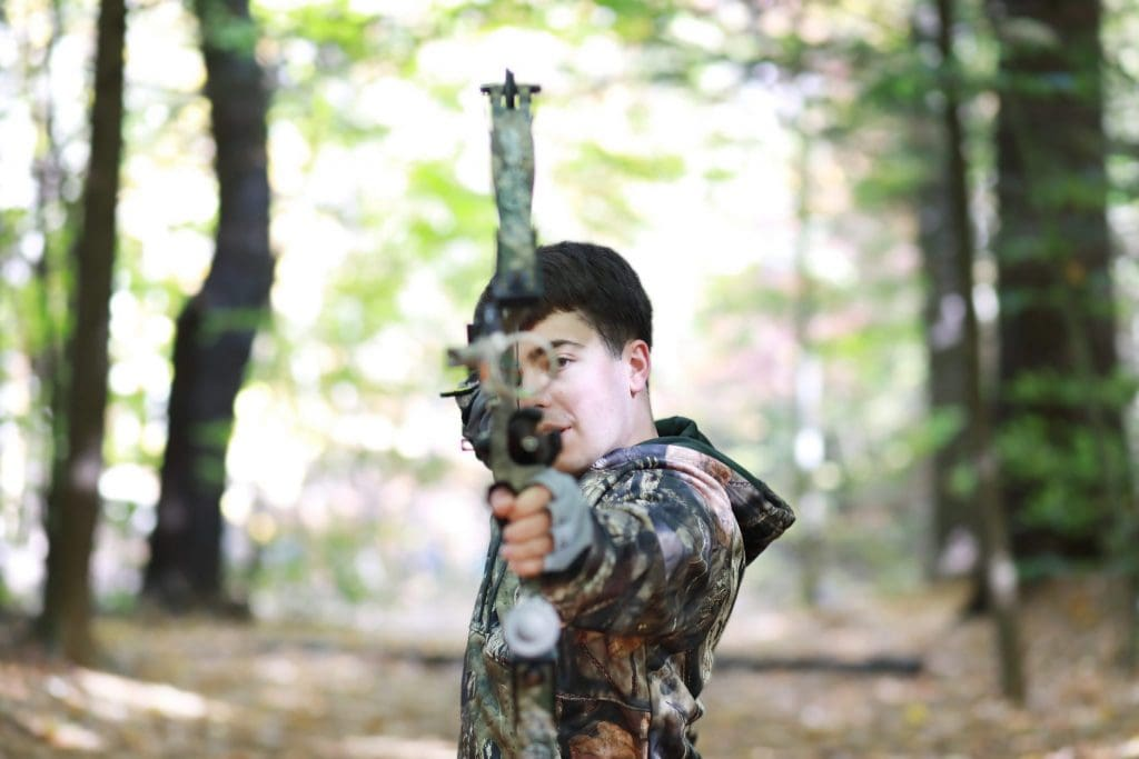 senior boy in camouflage jacket, holding bow and arrow, looking at the camera like he would shoot the bow and arrow in the woods.