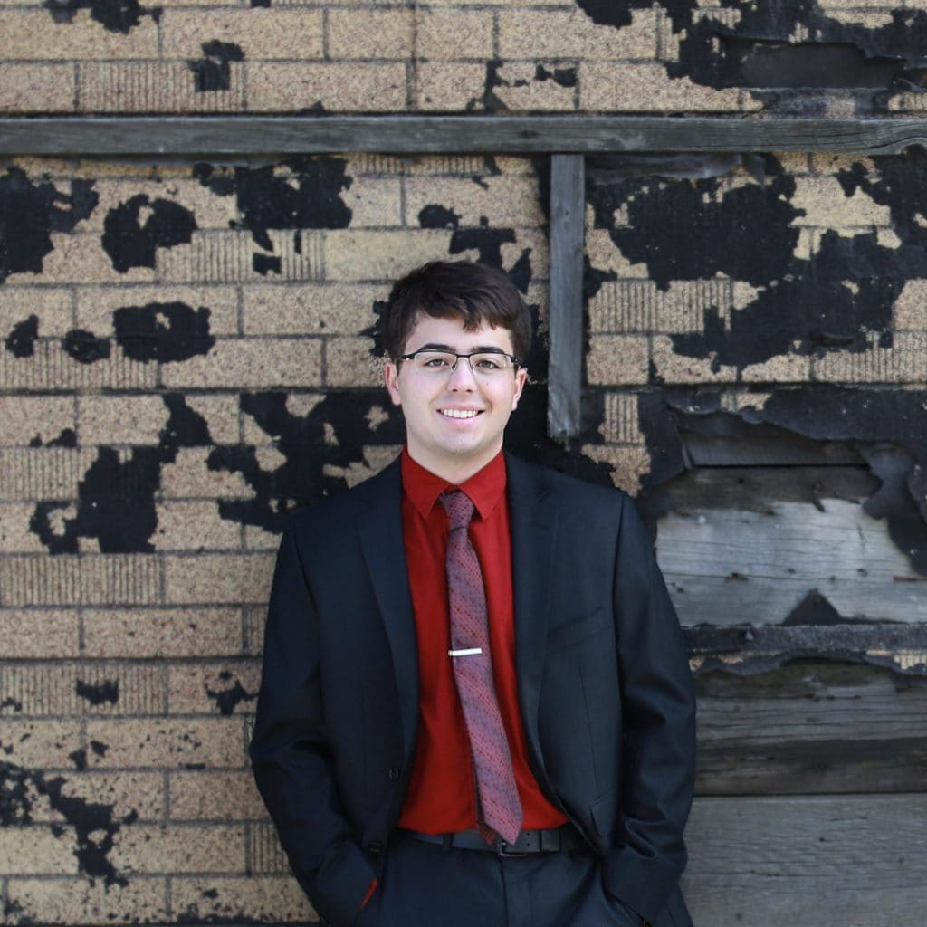 senior boy standing against textured building, black and brown in a black suit with a red shirt and red tie, wearing glasses