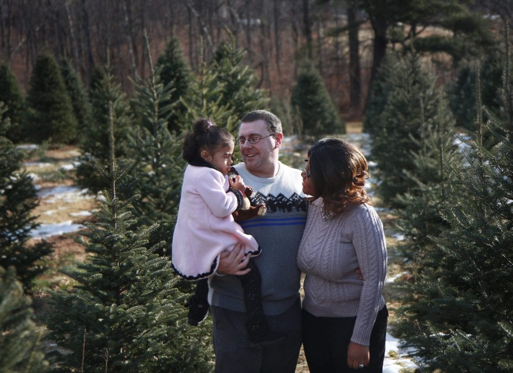 dad holding and looking at two year old daughter, wifes arm around her husband looking at her daughter, all standing in the tree farm
