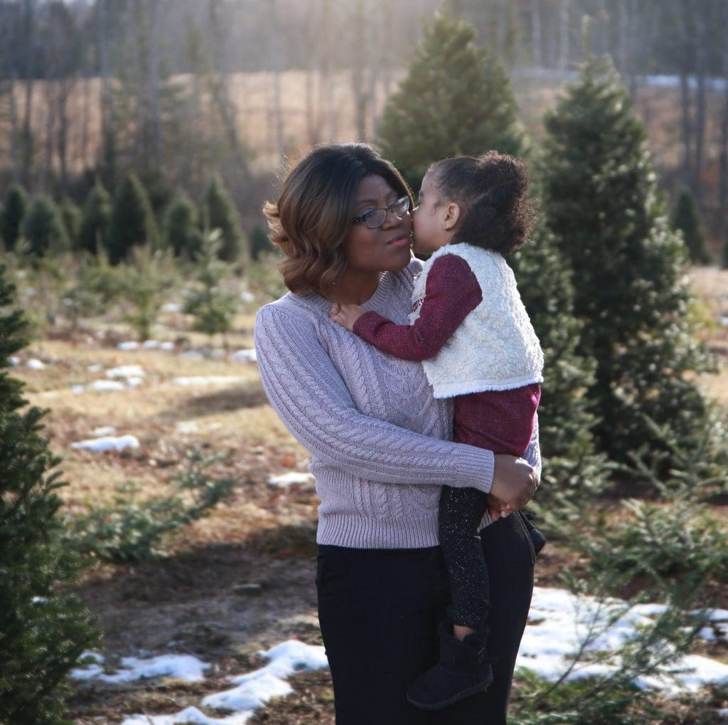 mom getting a kiss on the cheek from two year daughter in the tree farm