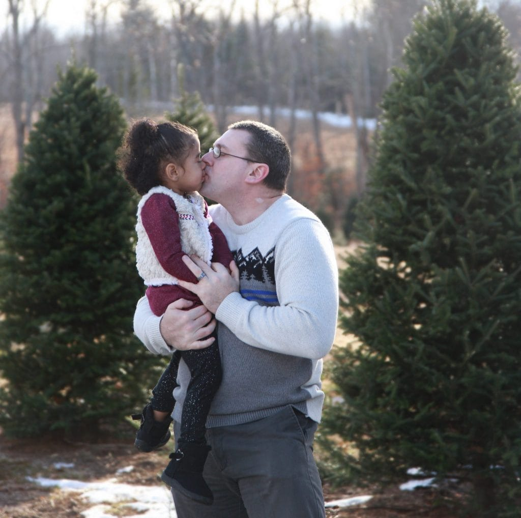 dad and two year old daughter kissing in the tree farm