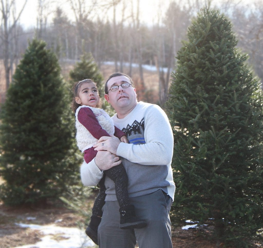 dad holding two year old daughter in the tree farm, both making a silly face.