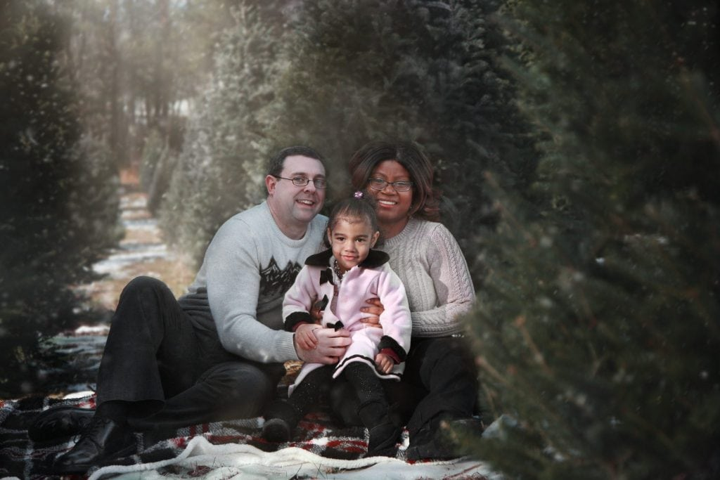 mom, dad, and two year daughter hugging each other sitting on a white blanket surrounded by trees in the tree farm, snow covered trees