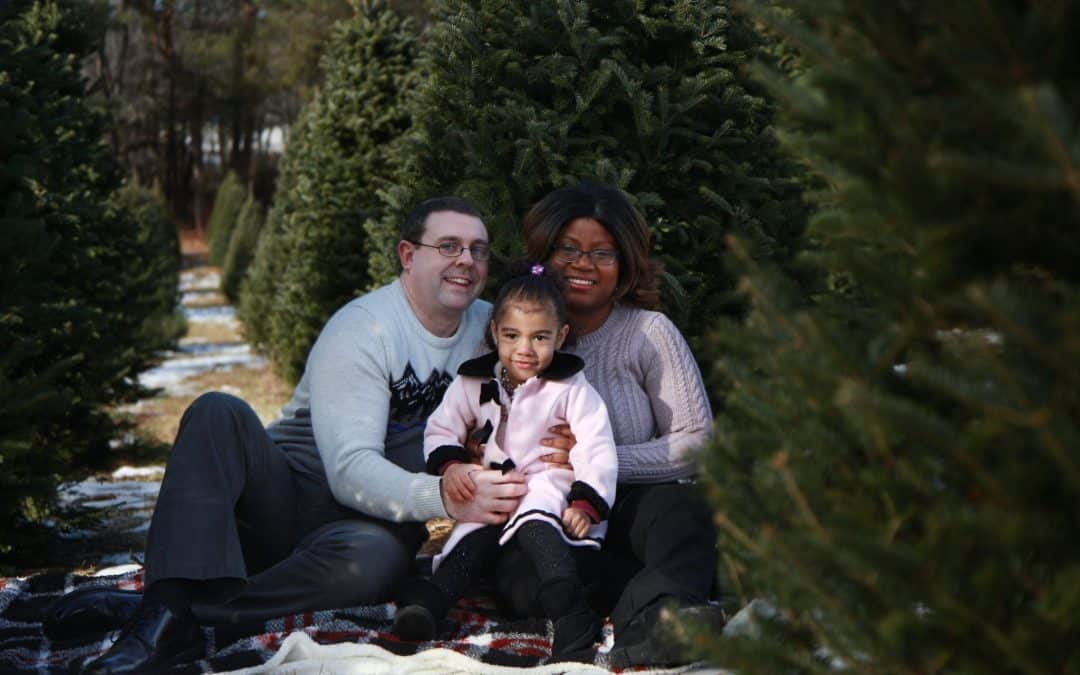 mom, dad, and two year old daughter sitting on a white blanket at a tree farm surrounded by trees hugging each other