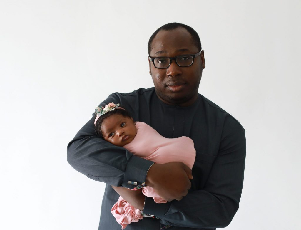 dad holding newborn daughter looking at the camera