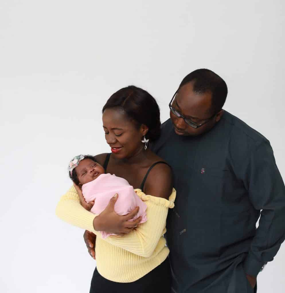 dad holding his wife, mother holding newborn daughter, both looking at newborn