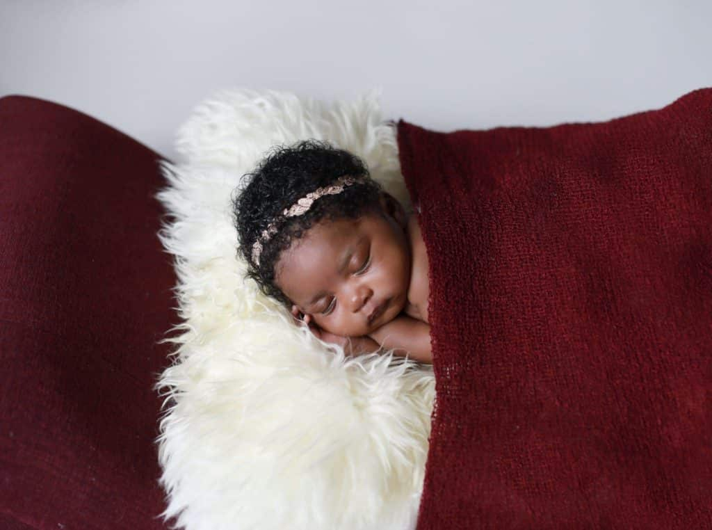 dark skinned newborn girl laying on stomach on red chase lounge, white fur, covered with a red wrap like a blanket, neutral headband