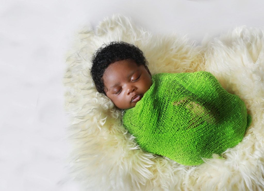 newborn girl wrapped in green wrap, on white fur